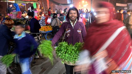 Market in India with man holding herbs