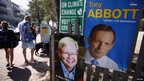 A man and his daughter with beach towels draped over their shoulders walk past election posters bearing pictures of Kevin Rudd (C) and Tony Abbott outside a polling station in Sydney on 7 September 2013