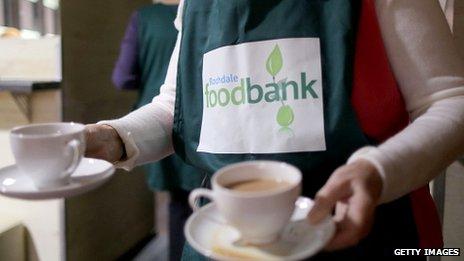 A foodbank worker serves tea