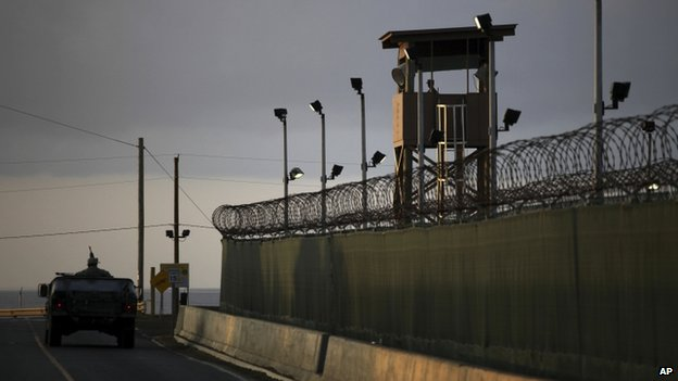 A US trooper stands in the turret of a vehicle with a machine gun, left, as a guard looks out from a tower at the detention facility of Guantanamo Bay