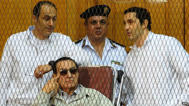 Egyptian toppled president Hosni Mubarak and his two sons Alaa (R) and Gamal stand behind bars during their trial at the Police Academy on September 14, 2013 in Cairo