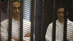 Gamal (L) and Alaa Mubarak, sons of former Egyptian President Hosni Mubarak, stand behind bars during their trial inside a dock at the police academy, on the outskirts of Cairo June 8, 2013.