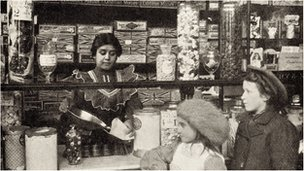 Two girls being served in a sweet shop
