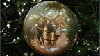 Family reflected in a tree decoration