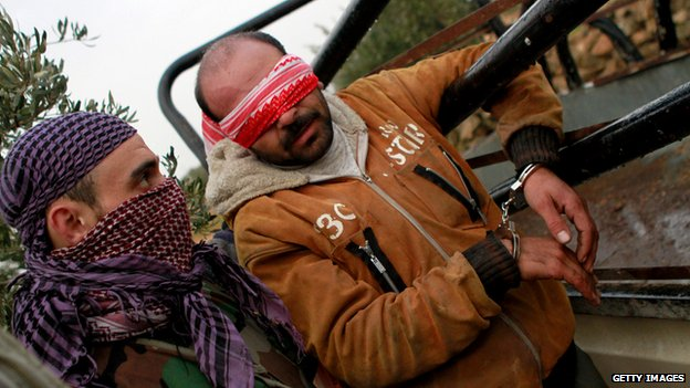 An unidentified man is blindfolded and arrested by Syrian rebels in January 2013