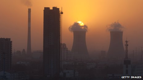 The sun sets behind chimneys in the city of Baoding, Hebei, 140 km south of Beijing