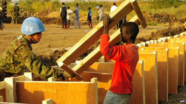 A peacekeeper and South Sudanese boy build a latrine at the UN House in Juba (17 December 2013)