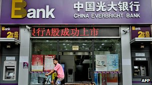A man cycles past a China Everbright Bank branch in Shanghai
