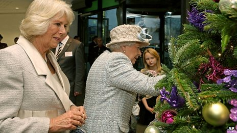 The Queen and Duchess of Cornwall hang decorations on a Christmas tree