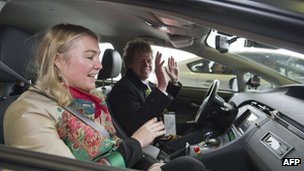 Woman sits in driverless car