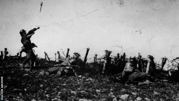 Two Germans drop behind cover, whilst a third hurls a hand grenade towards an Allied trench