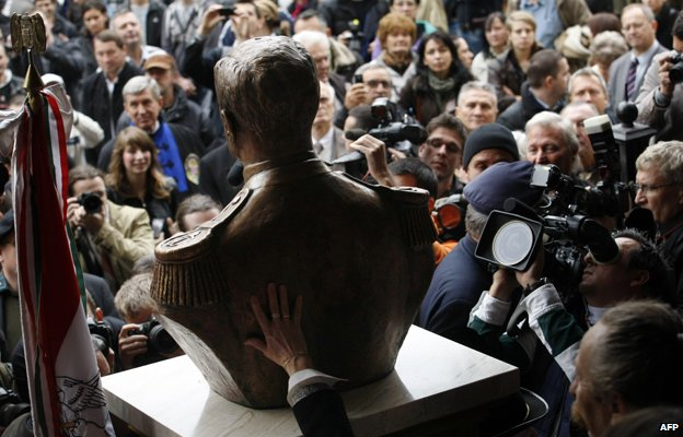 Photographers, cameramen and visitors crowd around a statue-bust of Hungary's wartime leader Miklos Horthy after it was unveiled in Budapest on November 3, 2013. The unveiling provoked protests of antifascist demonstrators.