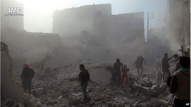 Syrians inspect the rubble of damaged buildings following a Syrian government airstrike in Aleppo on 17 December.