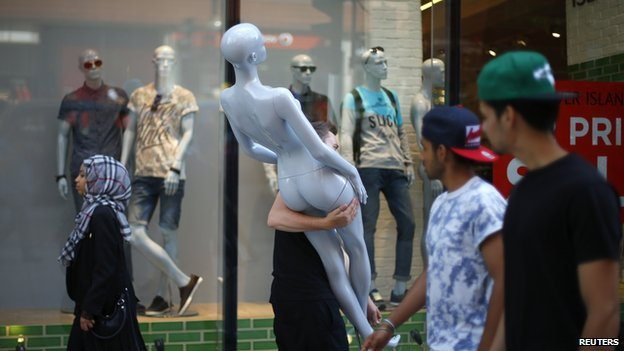 Shoppers pass a man carrying a shop window mannequin as he moves items to new premises on Oxford Street in London