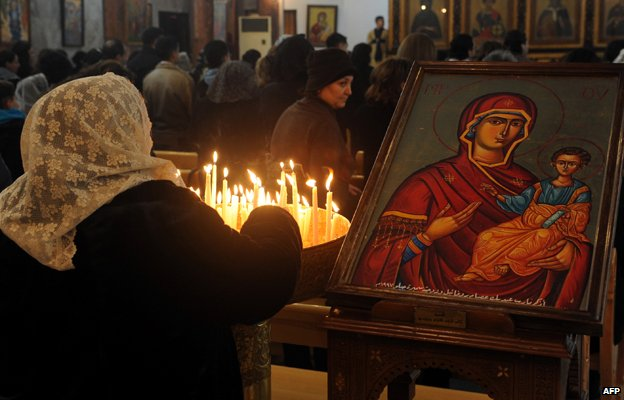 A Syrian woman lights candles as she attends early Christmas eve mass, at the Mar Elias (St. Elijah) Christian Orthodox church in Bab Tuma