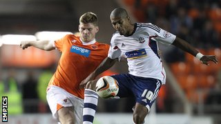 Blackpool defender Gary MacKenzie challenges Bolton striker Jermaine Beckford