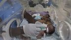 A nurse attends to four newly born babies squeezed in an incubator at a hospital in Nairobi, Kenya, on 19 December 2013