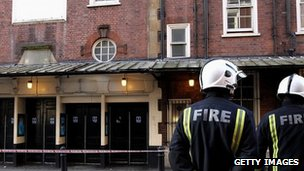 Firefighters stand outside the Apollo theatre