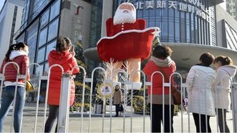 Women take pictures in front of a Santa Claus figure outside a shopping mall ahead of Christmas in Taiyuan