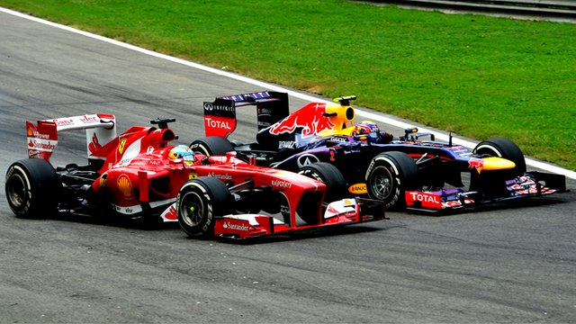 Ferrari's Fernando Alonso passes Red Bull Racing's Mark Webber during the Italian Grand Prix at Monza