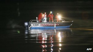 Police divers search the Dordogne river near Lugon for missing helicopter passengers on 20 December 2013