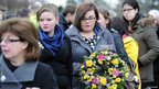Young people carry floral tributes to the ceremony