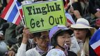 An anti-government protester blows a whistle and holds a placard in a rally at a major business district in Bangkok December 22, 2013