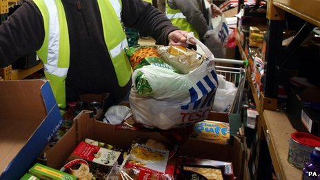 People in high-visibility yellow waistcoats pack food at a food bank