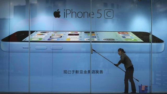 Worker cleaning in front of an iPhone 5c advertisement