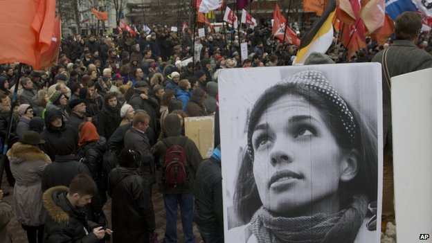 Demonstrators hold flags and a portrait, front, of jailed punk band Pussy Riot member Nadezhda Tolokonnikova, during an opposition rally in Moscow, Saturday, April 6, 2013