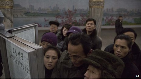 North Korean subway commuters gather around a public newspaper stand on the train platform in Pyongyang, North Korea to read the headlines about Chang Song-thaek, 13 December 2013