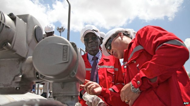 South Sudan's Minister for petroleum and mining prepares to press the button which will resume oil production after a 16-month hiatus in an oil production facility in Paloch in South Sudan's Upper Nile state, on 5 May 2013
