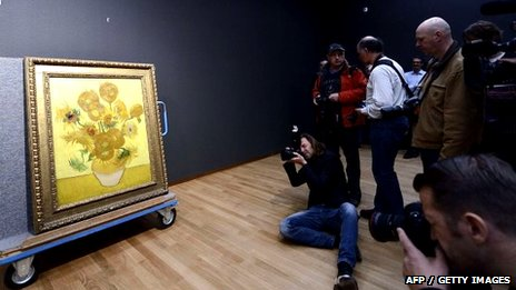 Photographers shoot pictures of the famous painting Sunflowers by Vincent Van Gogh