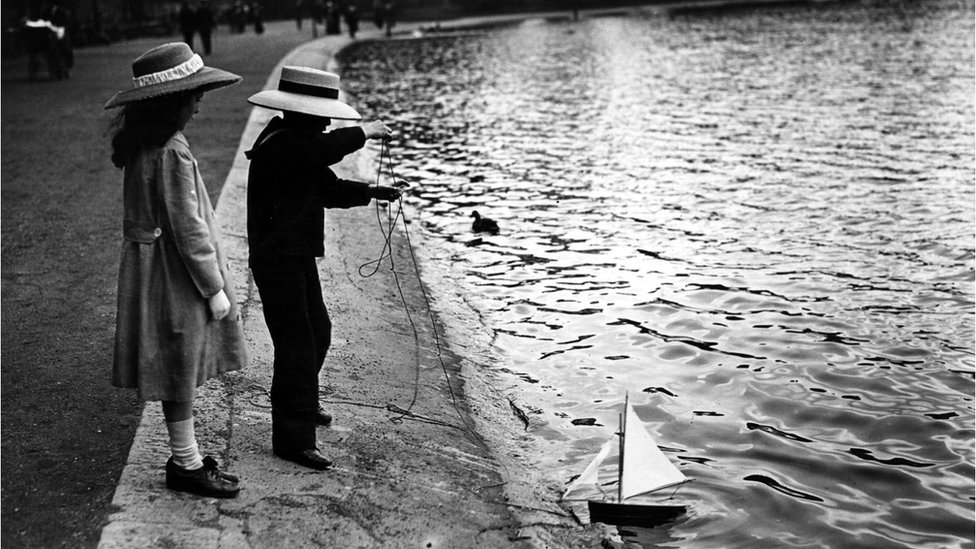 Two children playing with a small boat on the Serpentine, Hyde Park, London lake circa 1912