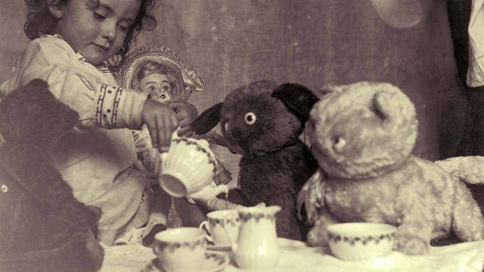A little girl hosts a tea party for her doll and three teddy bears circa 1915