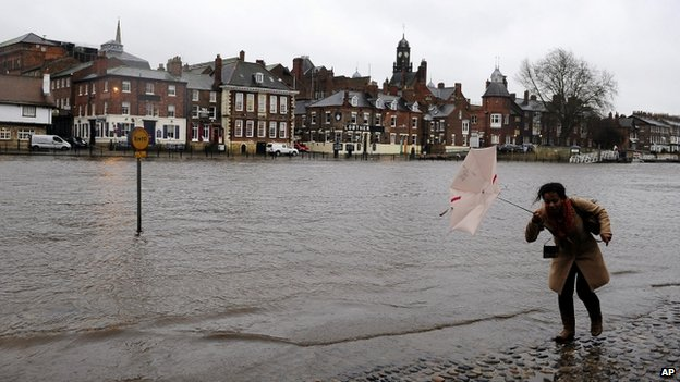 A woman walking down a riverside street in York flooded by the rising River Ouse