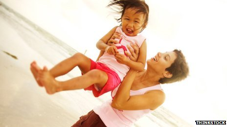 Woman holding young child on beach
