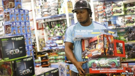 A man buys discounted toys in Caracas (15 Nov 2013)