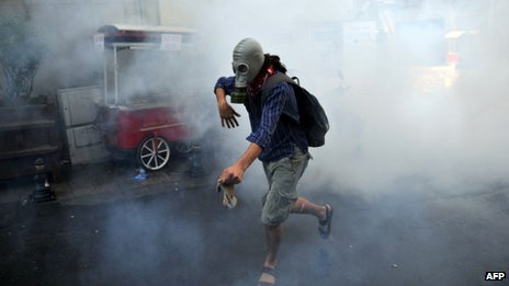 A demonstrator runs with gas mask as Turkish riot policemen use tear gas to disperse clashes on 31 May