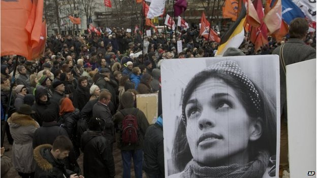 Demonstrators hold flags and a portrait, front, of jailed punk band Pussy Riot member Nadezhda Tolokonnikova, during an opposition rally in Moscow, April 6