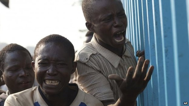 Young men reacts after their friend was badly injured by passing Chadian troops during a protest outside Mpoko Airport in Bangui, Central African Republic, Monday 23 December 2013