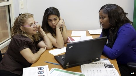 Certified enrolment specialist Richelle Baker, right, talks to Martha Medina, left, and her daughter Martha, both from Hialeah, Florida, at a Healthcare Insurance Marketplace office in Miami 20 December 2013