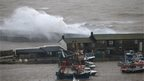 Storm waves break on the sea wall behind buildings on the Cobb in Lyme Regis