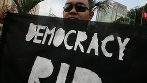 Man holds 'democracy RIP' banner