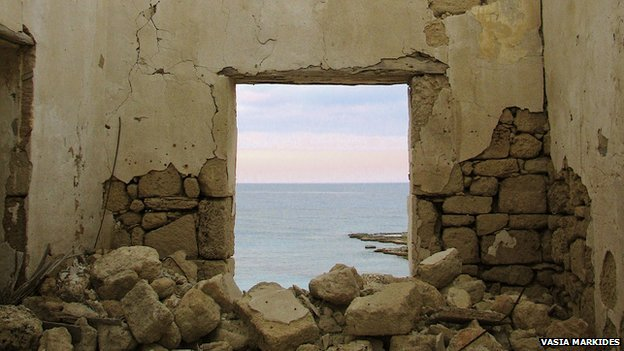 a view of the sea through a broken doorframe