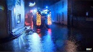 Fire crews in Usk, Monmouthshire work to clear a flooded street