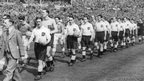 Bishop Auckland and Willington teams walk out at Wembley in 1950 in front of packed crowd.