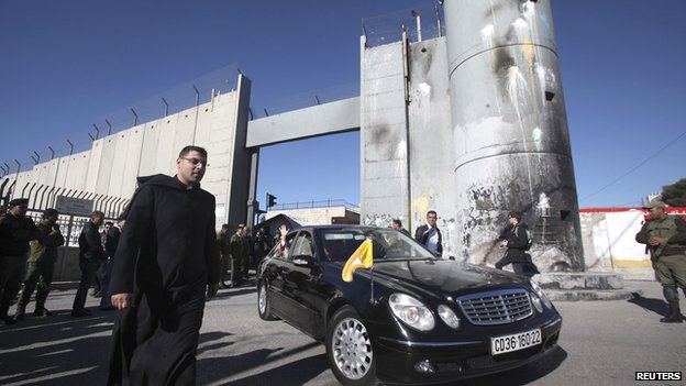 The Latin Patriarch of Jerusalem waves from a car as he is driven through an Israeli checkpoint into Bethlehem to attend Christmas celebrations