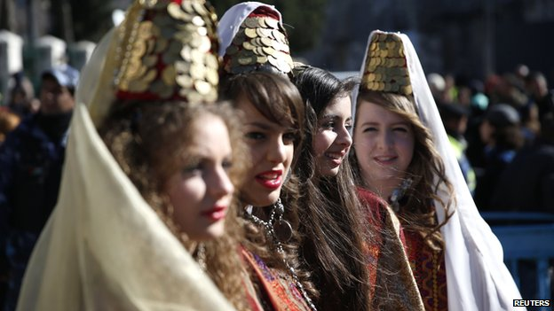 Young women wearing traditional Palestinian costumes take part in a Christmas procession at Manger Square in front of the Church of the Nativity, the site revered as the birthplace of Jesus, in the West Bank town of Bethlehem