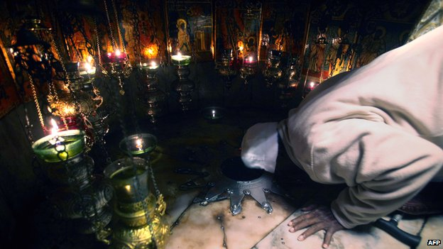 A Christian pilgrim prays inside the Grotto in the Church of the Nativity, traditionally believed to be the birthplace of Jesus Christ, during Christmas celebrations in the West Bank biblical town of Bethlehem